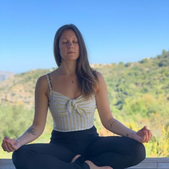 mujer meditando en solterreno en la casa de madera